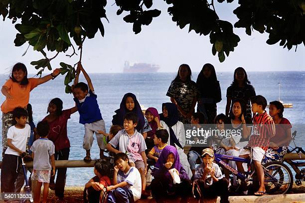 Malaysian children play at Flying Fish Cove Christmas Island with the Norwegian freighter MV Tampa in the background carrying around 460 refugees...