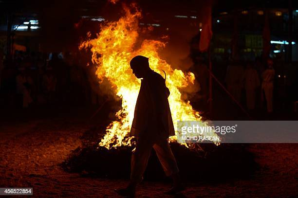A Malaysian Chinese devotee walks in front of a bed hot coals during the climax of the Nine Emperor Gods Festival in Ampang in the suburbs of Kuala...