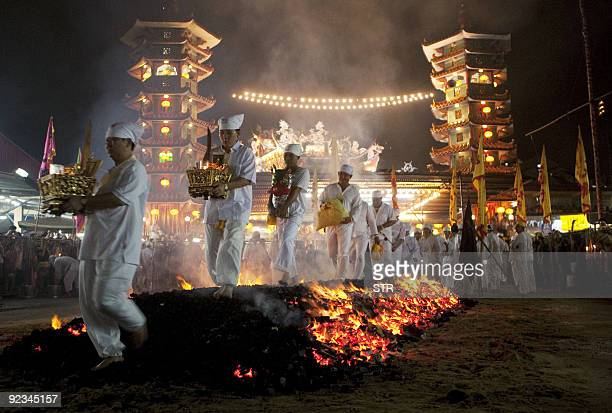 Malaysian Chinese devotees walk on a bed of hot coals on the last day of the Nine Emperor Gods religious festival at a temple in Kuala Lumpur on...