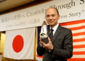 Malaysian designer Jimmy Choo holds his oneoff set of shoes using materials of Japan's Fukushima area during his lecture 'Creativity Thugh Skills' in...