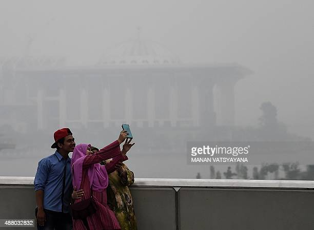 A Malaysian family poses for a 'selfie' with the backdrop of the Tuanku Mizan Zainal Abidin Mosque obscured by haze in Putrajaya on September 13 2015...