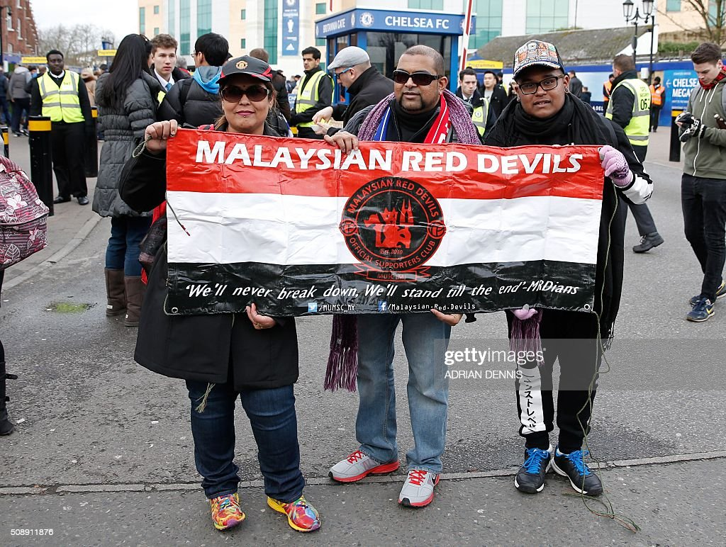 Malaysian fans pose for a picture before the English Premier League football match between Chelsea and Manchester United at Stamford Bridge in London on on February 7, 2016. / AFP / ADRIAN DENNIS / RESTRICTED TO EDITORIAL USE. No use with unauthorized audio, video, data, fixture lists, club/league logos or 'live' services. Online in-match use limited to 75 images, no video emulation. No use in betting, games or single club/league/player publications. /