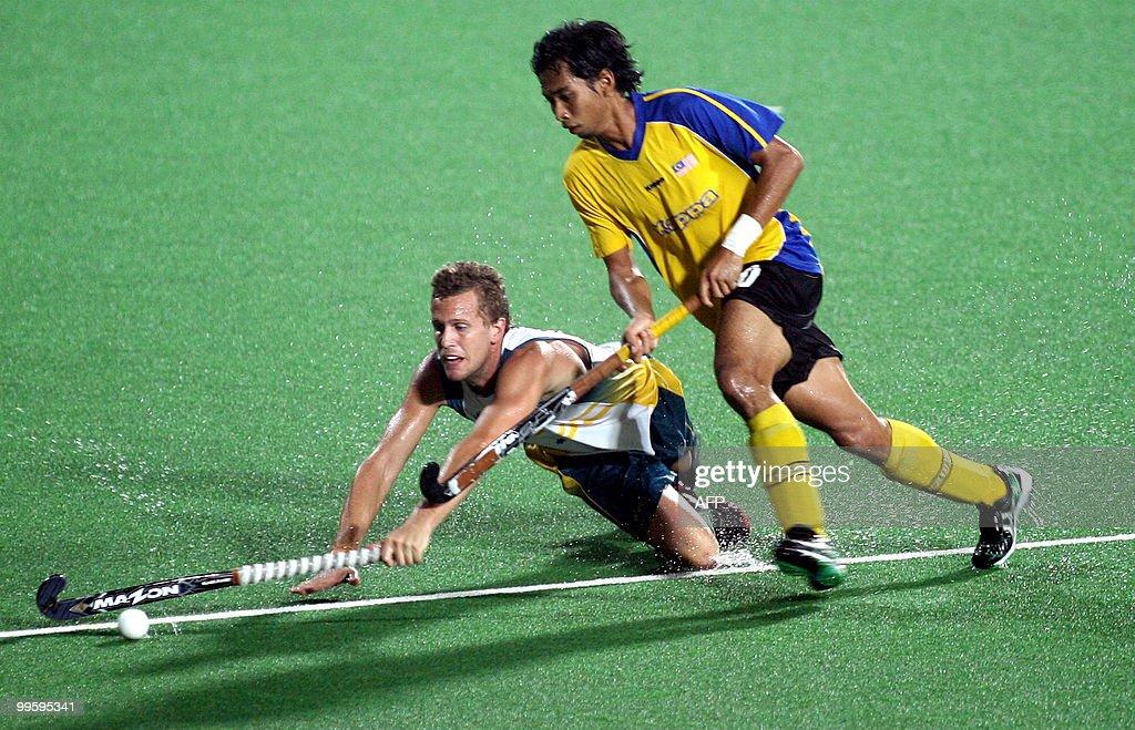 Malaysian field hockey player Hanafi Hafifi Hafiz challenges an Australian player for the ball during their match in the Sultan Azlan Shah Cup field...