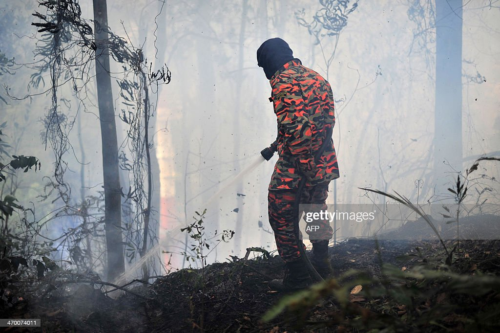 A Malaysian fireman douses a bushfire in Taman Bukit Melawati park in Kuala Lumpur on February 18, 2014. There were 312 bush fires reported nationwide on February 12 in just 24 hours during a dry spell this month in Malaysia, local media reported.