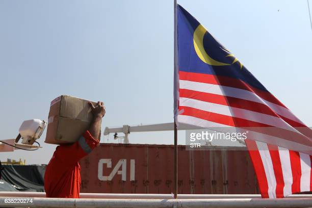 A Malaysian flag flies next to a worker unloading a box of relief aid for Rohingya Muslims delivered by the humanitarian aid Malaysian ship Nautical...
