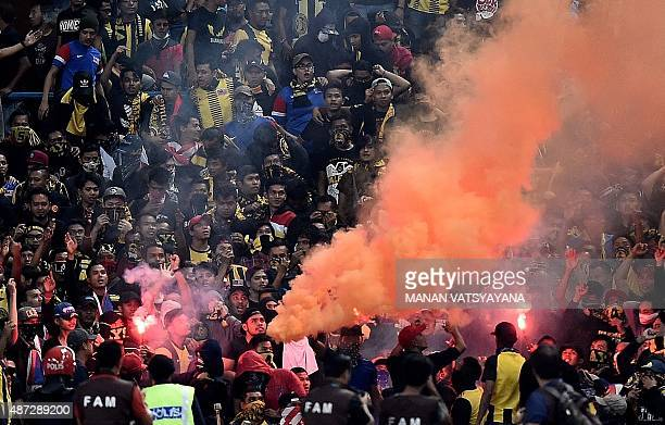 Malaysian football fans burn flares in the stands during the 2018 FIFA World Cup qualifying football match between Malaysia and Saudi Arabia in Shah...