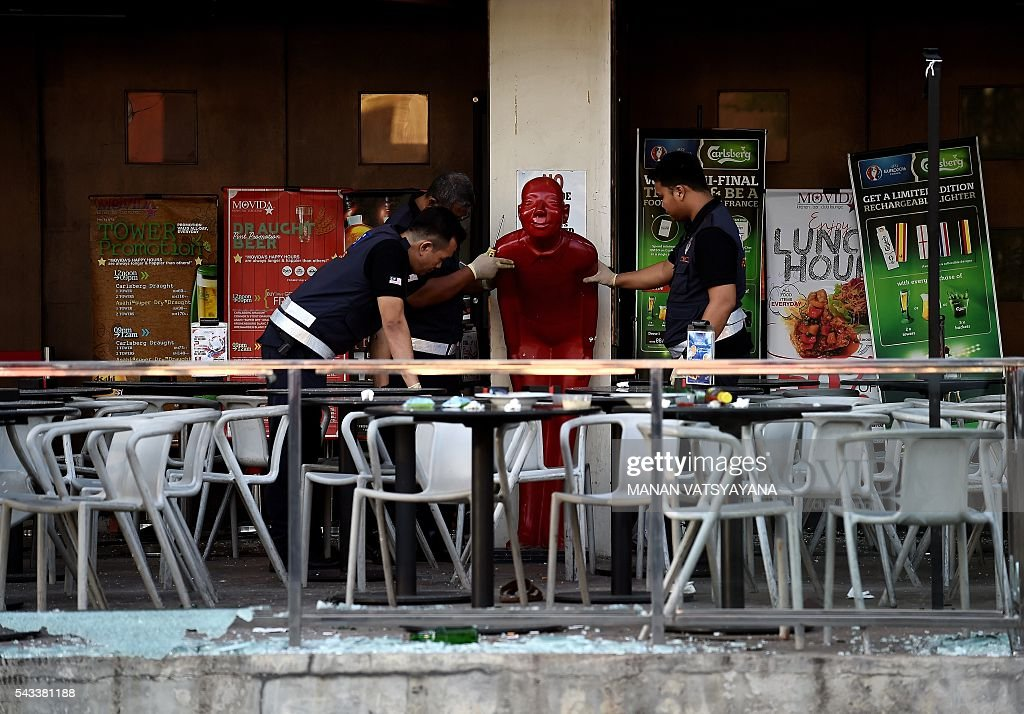 Malaysian forensic experts inspect the site of grenade attack at a restaurrant in Puchong district outside of Kuala Lumpur on June 28, 2016. Eight people were injured after a hand grenade was thrown at a restaurant in Malaysia's central Selangor state, police said, citing business rivalry rather than terrorism as the likely motive. / AFP / MANAN