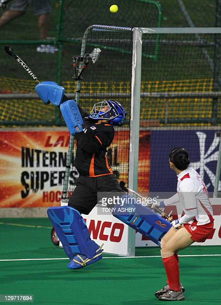 Malaysian goalkeeper Yahya Farah Ayunit attempts to stop India scoring a goal during their women's match at the Lanco International Super Series...