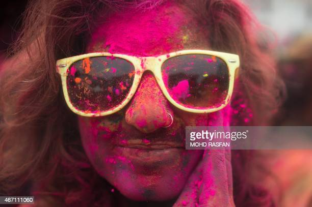 A Malaysian Hindu woman covered with coloured powders celebrates 'Holi' at a temple in Kuala Lumpur on March 21 2015 'Holi' the festival of colours...