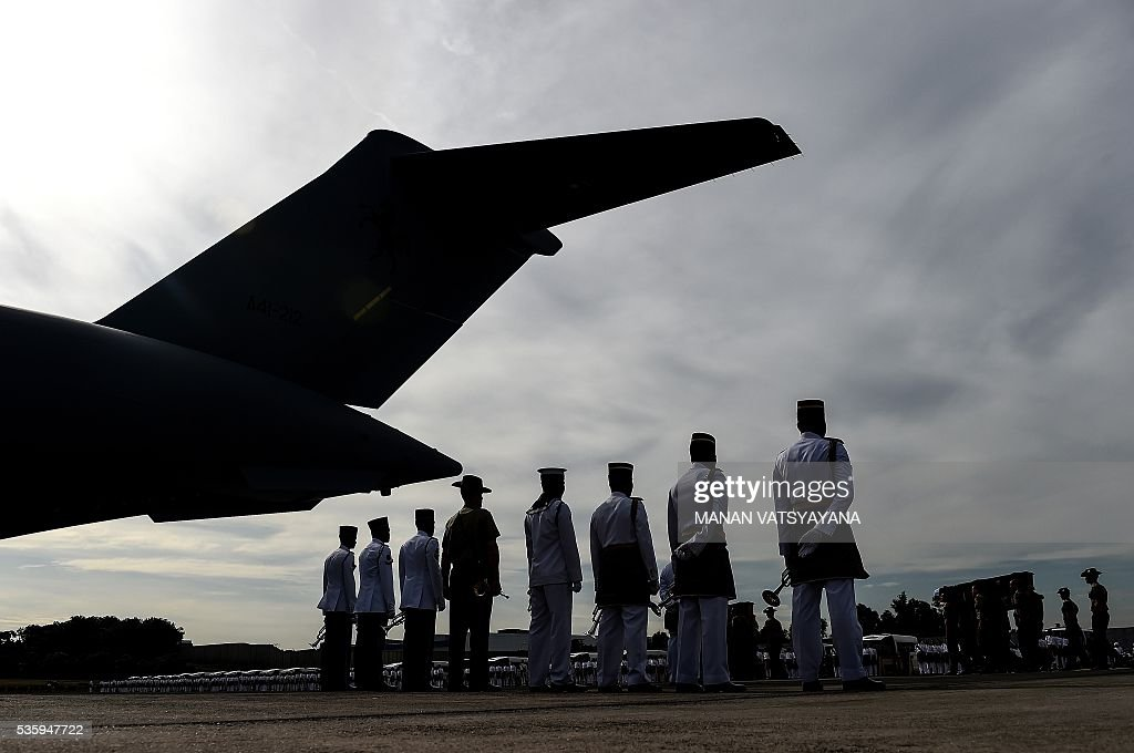 Malaysian honor guards stand guard as Australian military personell (R) carry the remains of their soldiers and dependents during a repatriation ceremony at the Royal Malaysian Airforce base in Subang on May 31, 2016. Decades after the end of the Vietnam war and the brutal fight against communists insurgency in Malaysia, the remains of 24 Australians soldiers and eight dependents were returned home. / AFP / MANAN