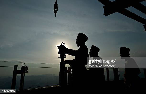 A Malaysian Islamic authority official sets up his theodolite to perform the 'Rukyah Hilal Syawal' the sighting of the new moon to determine the Eid...