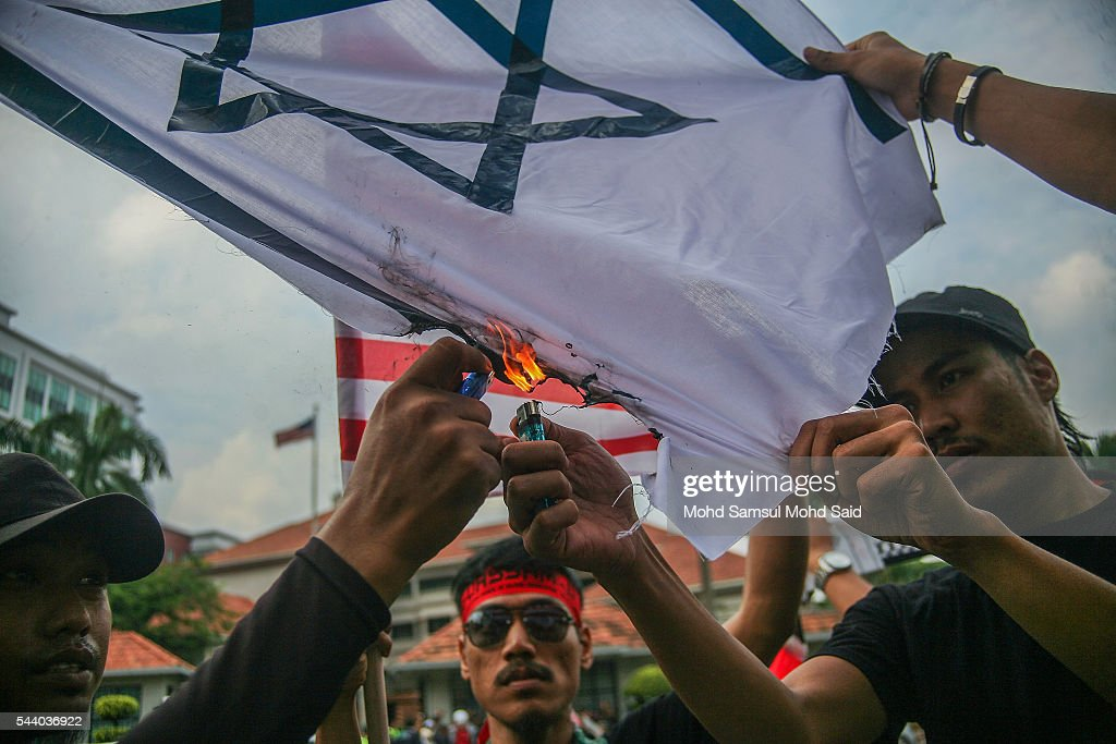 Malaysian Islamic NGO from Al-Quds Malaysia burn the Israel flag in front of the United States Embassy during a demonstration on International Quds Day on July 1, 2016 in Kuala Lumpur, Malaysia. International Quds day is an annual event held on the last Friday of the Holy month of Ramadan, as a means to express solidarity with the Palestinians. Jordans Sate Minister for Media Affairs condemned the storming of the Al-Aqsa mosque by Israeli settlers and police, saying that such actions are a violation of international law.