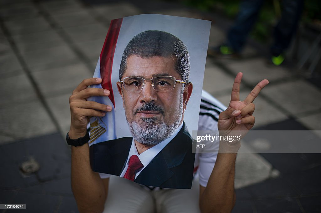 A Malaysian Islamist covers his face with a poster of ousted Egyptian President Mohamed Morsi during a protest to oppose the military overthrow of the Islamist leader and subsequent killings in Egypt, outside the Egyptian embassy in Kuala Lumpur on July 9, 2013. Fifty-one people, mostly Mohamed Morsi loyalists, were killed in Egypt on July 8 while rallying in favour of the ousted president, as the new rulers announced fresh elections by early 2014 amid US calls for restraint. AFP PHOTO / MOHD RASFAN