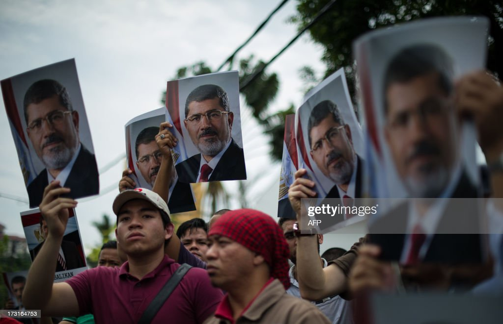 Malaysian Islamist demonstrator hold up posters of ousted Egyptian President Mohamed Morsi during a protest to oppose the military overthrow of the Islamist leader and subsequent killings in Egypt, outside the Egyptian embassy in Kuala Lumpur on July 9, 2013. Fifty-one people, mostly Mohamed Morsi loyalists, were killed in Egypt on July 8 while rallying in favour of the ousted president, as the new rulers announced fresh elections by early 2014 amid US calls for restraint.