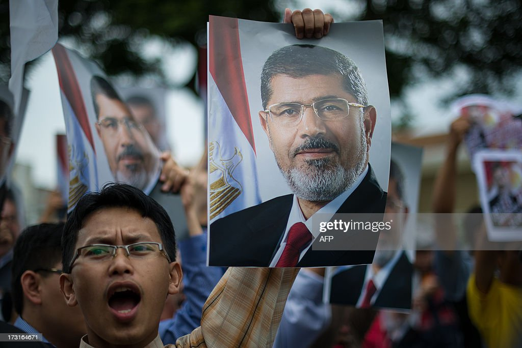 A Malaysian Islamist demonstrator shouts slogans as he holds a poster of ousted Egyptian President Mohamed Morsi during a protest to oppose the military overthrow of the Islamist leader and subsequent killings in Egypt, outside the Egyptian embassy in Kuala Lumpur on July 9, 2013. Fifty-one people, mostly Mohamed Morsi loyalists, were killed in Egypt on July 8 while rallying in favour of the ousted president, as the new rulers announced fresh elections by early 2014 amid US calls for restraint.