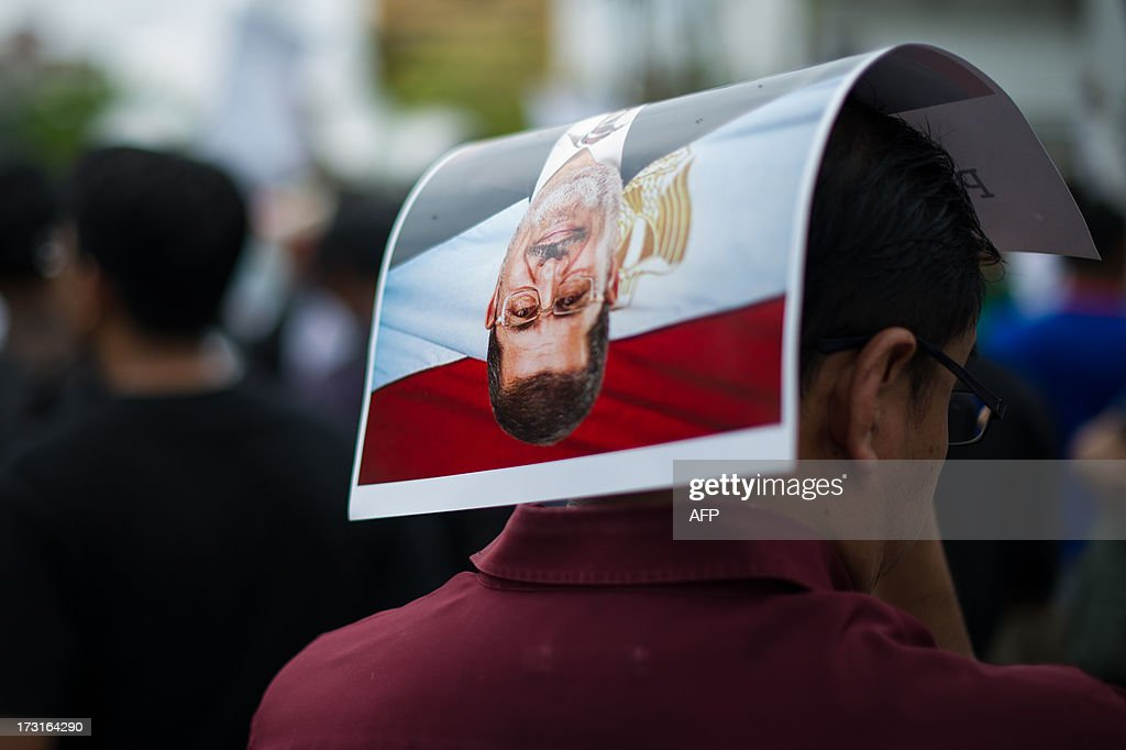 A Malaysian Islamist protester holds a poster of ousted Egyptian President Mohamed Morsi during a protest to oppose the military overthrow of the Islamist leader and subsequent killings in Egypt, outside the Egyptian embassy in Kuala Lumpur on July 9, 2013. Fifty-one people, mostly Mohamed Morsi loyalists, were killed in Egypt on July 8 while rallying in favour of the ousted president, as the new rulers announced fresh elections by early 2014 amid US calls for restraint.