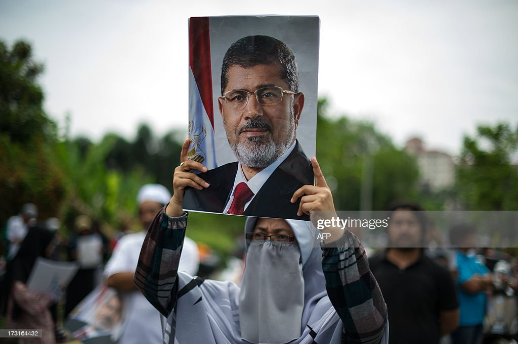 A Malaysian Islamist protester holds a poster of ousted Egyptian President Mohamed Morsi during a protest to oppose the military overthrow of the Islamist leader and subsequent killings in Egypt, outside the Egyptian embassy in Kuala Lumpur on July 9, 2013. Fifty-one people, mostly Mohamed Morsi loyalists, were killed in Egypt on July 8 while rallying in favour of the ousted president, as the new rulers announced fresh elections by early 2014 amid US calls for restraint. AFP PHOTO / MOHD RASFAN