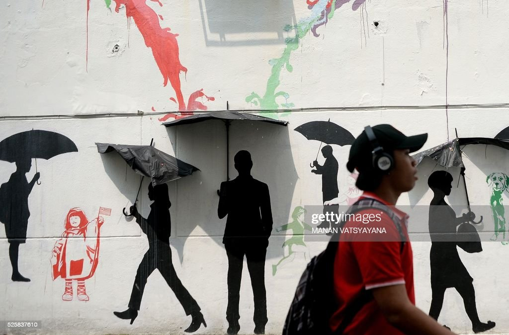 A Malaysian man walks past a mural on a street in Kuala Lumpur on April 29, 2016. / AFP / MANAN