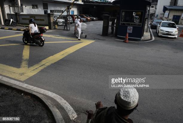 A Malaysian man watches as hospital workers move a body cart through the gate of the forensics wing of the Hospital Kuala Lumpur where the body of...