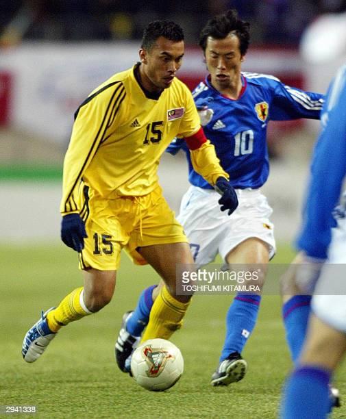 Malaysian midfielder and captain Tengku Hazman battles for a ball with Japan's Toshiya Fujita during their friendship match in Kashima stadium some...