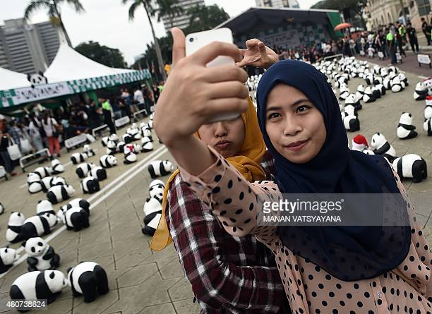 Malaysian muslim girls take a selfie as they pose with some of the 1600 papiermache pandas displayed at Independence Square in Kuala Lumpur on...