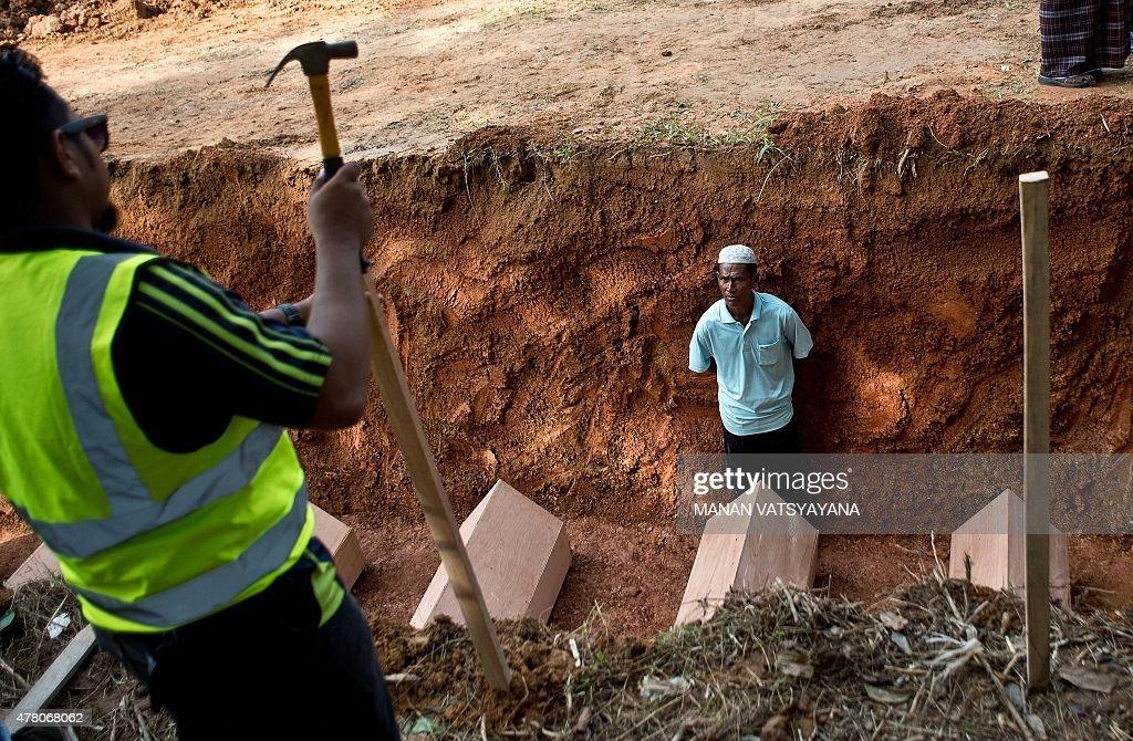 A Malaysian Muslim man looks on inside a pit during the reburial of remains believed to be those of ethnic Rohingya found at humantrafficking camps...