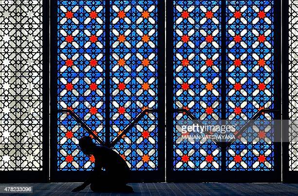 A Malaysian Muslim man offers prayers during the holy Islamic month of Ramadan at the Sultan Salahuddin Abdul Aziz Shah Mosque in Shah Alam on June...