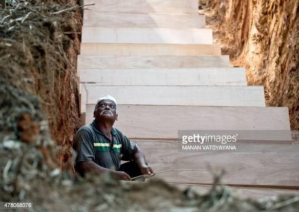 A Malaysian Muslim man sits amid coffins in a pit during the reburial of remains believed to be those of ethnic Rohingya found at humantrafficking...