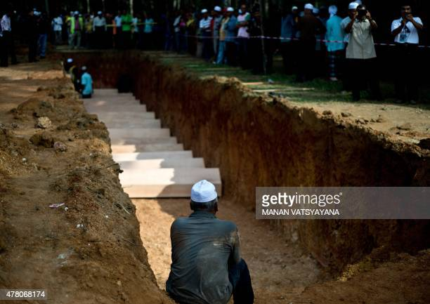 A Malaysian Muslim man sits near a pit during the reburial of remains believed to be those of ethnic Rohingya found at humantrafficking camps in the...