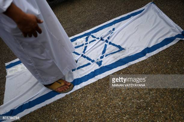 A Malaysian Muslim man steps on the Israeli flag during a solidarity protest after Friday prayers outside the National Mosque in Kuala Lumpur on July...