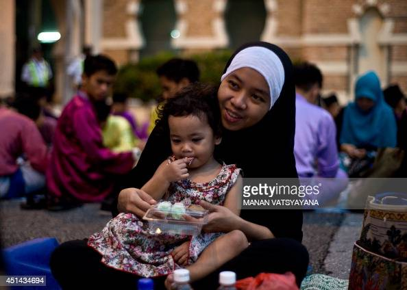 A Malaysian Muslim woman feeds her child as they break their fast on the first day of the holy Islamic month of Ramadan in Kuala Lumpur on June 29...