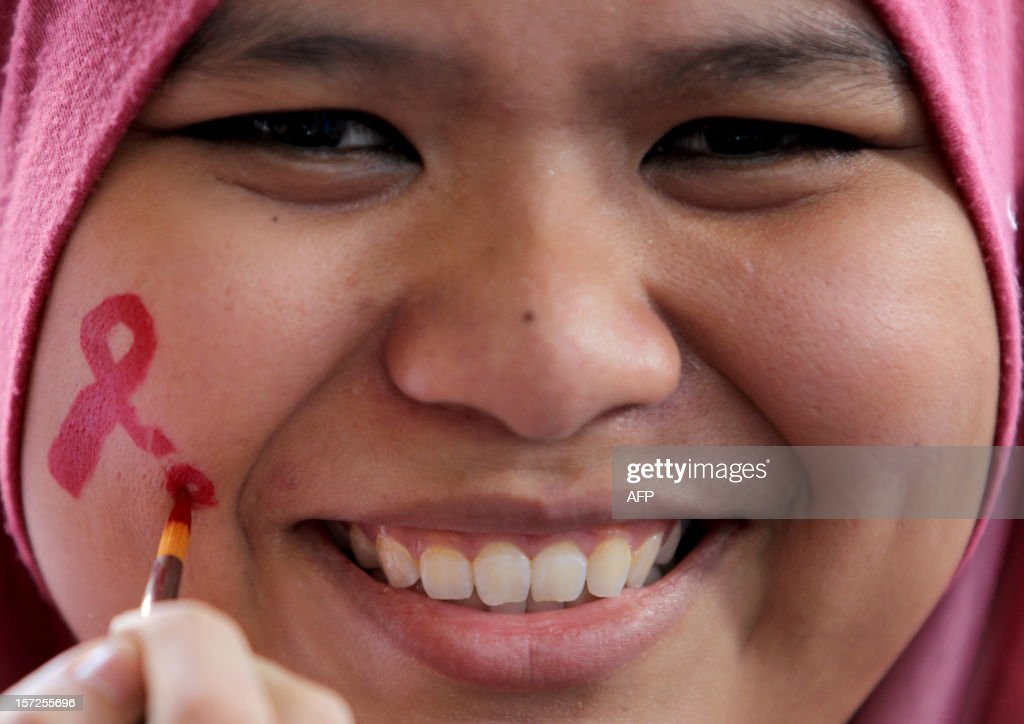 A Malaysian Muslim woman has her face painted during a World Aids Day campaign in Kuala Lumpur on December 1, 2012. World AIDS Day is celebrated on December 1 each year around the world. AFP PHOTO / MOHD RASFAN
