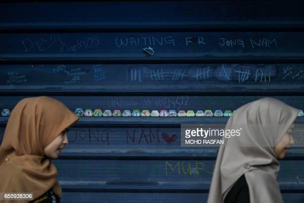 Malaysian Muslim women walk past graffiti referring to Kim JongNam the halfbrother of North Korean leader Kim JongUn on the wall opposite the...