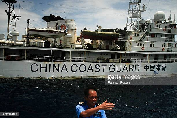 Malaysian Navy personel gestures towards the ship's captain as they approach a vessel belonging to the Chinese Coast Guard during an exchange of...