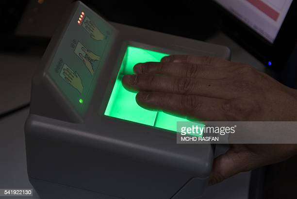 A Malaysian official from the United Nations High Commissioner for Refugees gives a demonstration on a fingerprint scanner to be used for refugees...