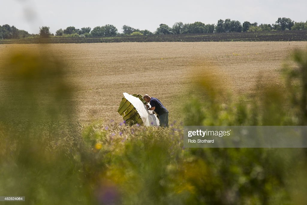 A Malaysian official inspects wreckage of Malaysia Airlines flight MH17 during monitoring by investigators from Malaysia and the Organization for Security and Co-operation in Europe on July 22, 2014 in Grabovo, Ukraine. Malaysia Airlines flight MH17 was travelling from Amsterdam to Kuala Lumpur when it crashed killing all 298 on board including 80 children. The aircraft was allegedly shot down by a missile and investigations continue over the perpetrators of the attack.