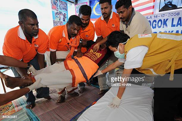 Malaysian paramedics and ethnic Indians carry away an activist who bacame weak during a hunger strike to hospital at Sri Maha Kaliamman temple in...