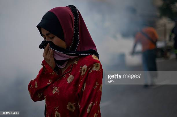 A Malaysian pedestrian protects her face while engulfed in a cloud of pesticide during a dengue prevention spraying in Ampang in the suburbs of Kuala...