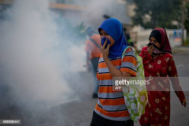 Malaysian pedestrians protect their noses while engulfed in a cloud of pesticide during a dengue prevention spraying in Ampang in the suburbs of...