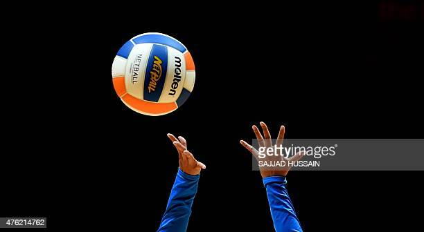 Malaysian players reach for the ball while playing against Singapore in the women's netball final match at the 28th Southeast Asian Games in...