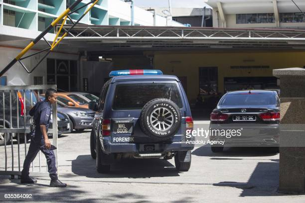 Malaysian police officer guards the entrance to the Institute of Forensic Medicine of Kuala Lumpur Hospital as a Forensic Police car enters the gate...