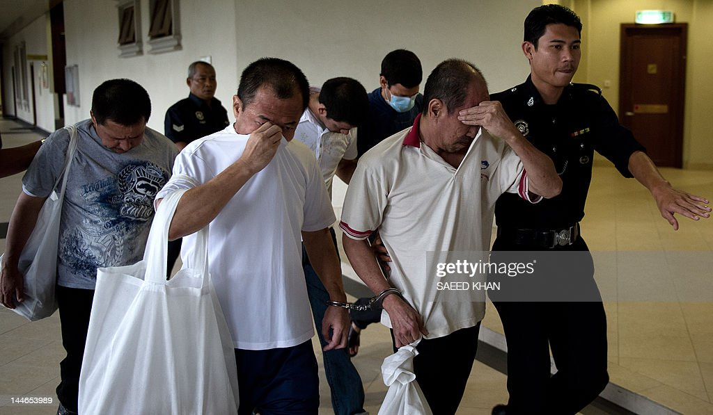 Malaysian police officers escort Singaporean Lim Hung Wang (2nd L), Malaysian Lee Boon Siah (2nd R) along with Mexican brothers (back row) Luis Alfonso Gonzalez Villarreal (L), Jose Regino Gonzalez Villarreal (C) and Simon Gonzalez Villarreal towards the court room in Kuala Lumpur on May 17, 2012. Three Mexican brothers were sentenced to death by hanging in Malaysia on May 17 for their part in a methamphetamine production operation. AFP PHOTO / Saeed Khan
