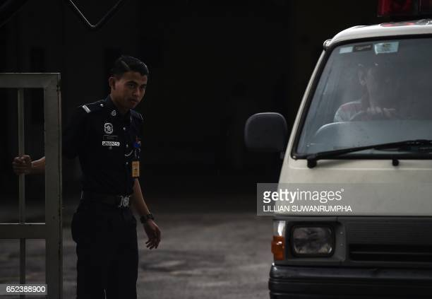 A Malaysian policeman opens the gate of the forensics wing of the Hospital Kuala Lumpur where the body of Kim JongNam lies in Kuala Lumpur on March...