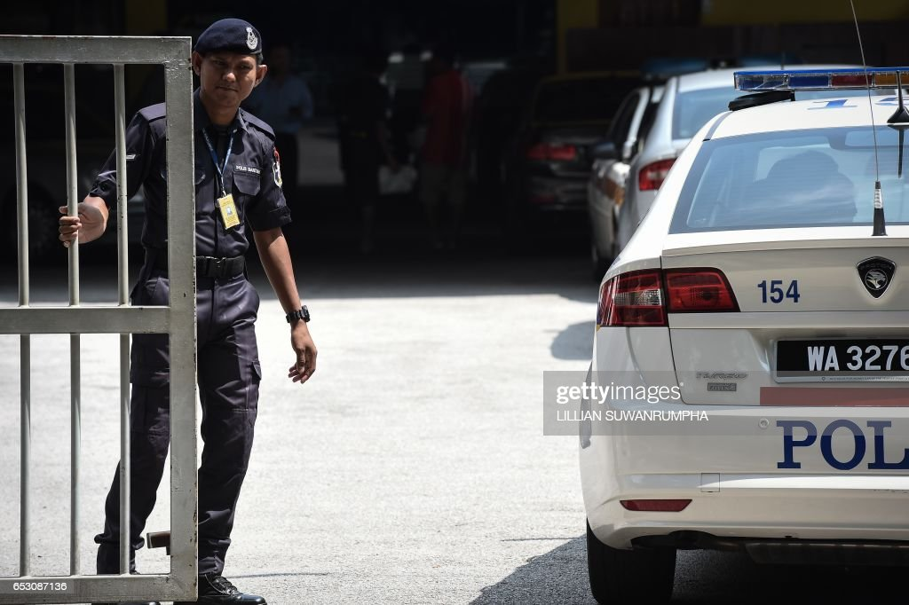 A Malaysian policeman opens the gate to the forensics wing of the Hospital Kuala Lumpur, where the body of Kim Jong-Nam is being held, in Kuala Lumpur on March 14, 2017. The killing of the half-bro...