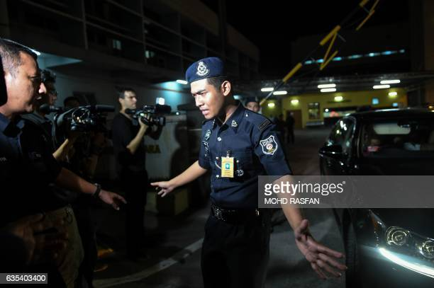 A Malaysian policeman tries to stop members of the media as a North Korean embassy official leaves the Forensic department where the body of a North...