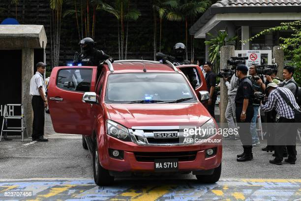 Malaysian policemen escort a fourwheel drive believed to be carrying Vietnamese national Doan Thi Huong and Indonesian national Siti Aisyah after a...