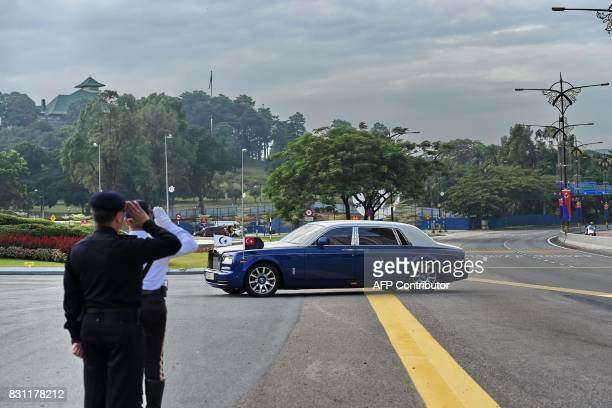 Malaysian policemen salute as a RollsRoyce belonging to the Sultan of Johor enters the Istana Bukit Serene palace in Johor Bahru on August 14 for the...
