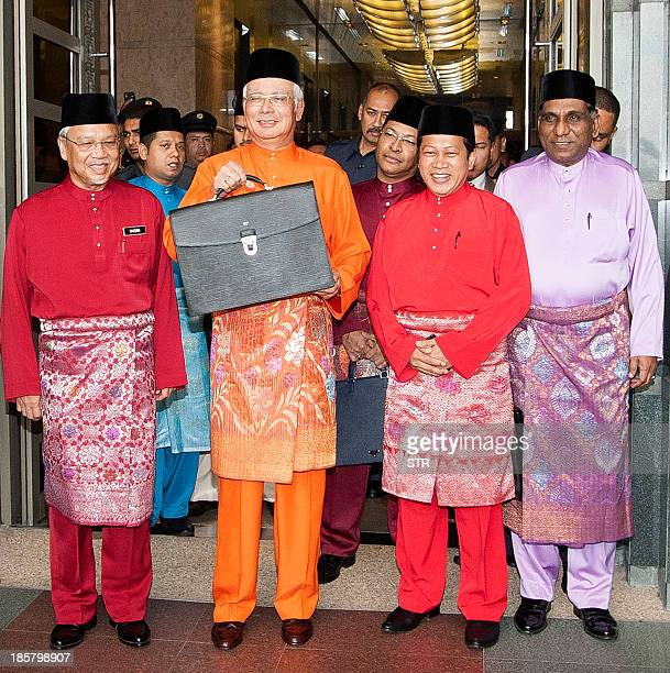 Malaysian Prime Minister and Finance Minister Najib Razak holds a briefcase containing Malaysia's 2014 budget as he leaves the Finance Ministry...