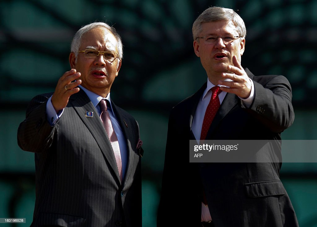Malaysian Prime Minister Najib Razak (L) and Canada's Prime Minister Stephen Harper (R) gesture during a photo call at the top steps of the prime minister's office in Putrajaya on October 6, 2013. Harper arrived for a visit to hold talks with the Malaysian leadership on bilateral and international issues. AFP PHOTO / MOHD RASFAN