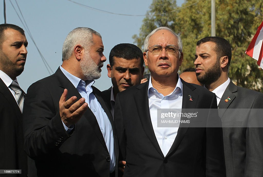 Malaysian Prime Minister Najib Razak (C) and Gaza's Hamas prime minister Ismail Haniya (L) are seen at the government building, destroyed during the Israeli and Hamas conflict November 14-21, 2012, in Gaza city on January 22, 2013. Razak pledged solidarity with the Palestinians on his first trip to Gaza, and backed reconciliation efforts between Hamas and Fatah.